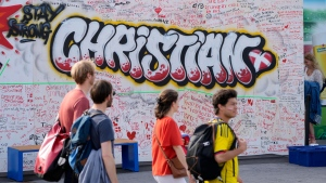 People wrote well wishes at a graffiti for Danish player Christian Eriksen on a wall at the fanzone in Copenhagen, Denmark, Monday, June 14, 2021. Eriksen remains in hospital after he collapsed on the pitch during the European Championship game against Finland on Saturday and needed CPR from medical staff before regaining consciousness. (AP Photo/Martin Meissner)