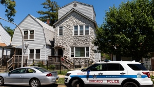Chicago police keep watch and crime scene tape hangs outside a house in the 6200 block of South Morgan, where multiple people were shot, some fatally, inside the Englewood building, Tuesday afternoon, June 15, 2021, in Chicago. An argument in the house on Chicago's South Side erupted into gunfire early Tuesday. (Ashlee Rezin Garcia/Chicago Sun-Times via AP)