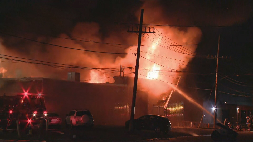 Flames and smoke are visible at the scene of a bakery fire in Etobicoke Tuesday, June 15, 2021.