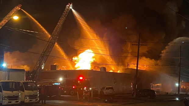 Flames and smoke are visible at the scene of a bakery fire in Etobicoke Tuesday, June 15, 2021. (Tristan Phillips /CP24)
