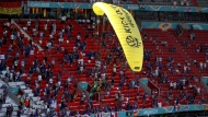 A Greenpeace paraglider lands in the stadium prior to the Euro 2020 soccer championship group F match between France and Germany at the Allianz Arena stadium in Munich, Tuesday, June 15, 2021. (AP Photo/ctivist Alexander Hassenstein, Pool)