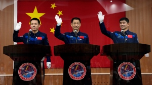 Chinese astronauts, from left, Tang Hongbo, Nie Haisheng, and Liu Boming wave during a press conference at the Jiuquan Satellite Launch Center ahead of the Shenzhou-12 launch from Jiuquan in northwestern China, Wednesday, June 16, 2021. China plans on Thursday to launch three astronauts onboard the Shenzhou-12 spaceship, who will be the first crew members to live on China's new orbiting space station Tianhe, or Heavenly Harmony from the Jiuquan Satellite Launch Center in northwest China. (AP Photo/Ng Han Guan)