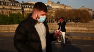 FILE - In this March 29, 2021 file photo, A man walks with a face mask to prevent the spread of the COVID-19 coronavirus, as a man takes a snapshot of the sunset, in Paris. France is lifting mandatory mask-wearing outdoors and will halt an eight-month nightly coronavirus curfew on June 20. (AP Photo/Thibault Camus, File)
