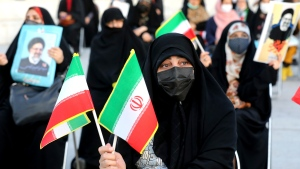 A supporter of presidential candidate Ebrahim Raisi holds Iranian flags during a rally in Tehran, Iran, Monday, June 14, 2021. Iran's clerical vetting committee has allowed just seven candidates for the Friday, June 18, ballot, nixing prominent reformists and key allies of President Hassan Rouhani. The presumed front-runner has become Raisi, the country's hard-line judiciary chief who is closely aligned with Supreme Leader Ayatollah Ali Khamenei. (AP Photo/Ebrahim Noroozi)