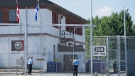 Guards stand outside the gates of an immigrant holding centre in Laval, Que., Monday, August 15, 2016. Immigration holding facilities in Vancouver and Laval, Que., will be replaced as part of a $138-million overhaul intended to improve detention conditions for newcomers to Canada, according to Public Safety Minister Ralph Goodale. THE CANADIAN PRESS/Graham Hughes