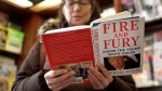 """Susan Mallin, from Glenview, Ill., looks over a copy of the book """"Fire and Fury: Inside the Trump White House"""" by Michael Wolff at Barbara's Books Store, Friday, Jan. 5, 2018, in Chicago. (AP Photo/Charles Rex Arbogast)"""