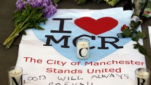 """FILE - In this Tuesday May 23, 2017 file photo, a sign with flowers and candles are placed after a vigil in Albert Square, Manchester, England, the day after the suicide attack at an Ariana Grande concert that left 22 people dead. A public inquiry into a mass attack at a 2017 Ariana Grade concert in northwest England concluded Thursday June 17, 2021, that """"serious shortcomings"""" by venue operators, security staff and police helped a suicide bomber who killed 22 people carry out his """"evil intentions."""" (AP Photo/Kirsty Wigglesworth, File)"""