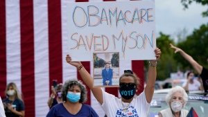 Adelys Ferro holds a sign in support of Obamacare as former President Barack Obama speaks while campaigning for Democratic presidential candidate former Vice President Joe Biden at Florida International University, Saturday, Oct. 24, 2020, in North Miami, Fla. (AP Photo/Lynne Sladky)