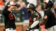 Baltimore Orioles' Cedric Mullins, center, celebrates with Austin Hays, left, and Maikel Franco after hitting a three-run home run off Toronto Blue Jays relief pitcher Jeremy Beasley during the eighth inning of a baseball game, Friday, June 18, 2021, in Baltimore. The Orioles won 7-1. Franco and Pedro Severino scored on the home run. (AP Photo/Julio Cortez)