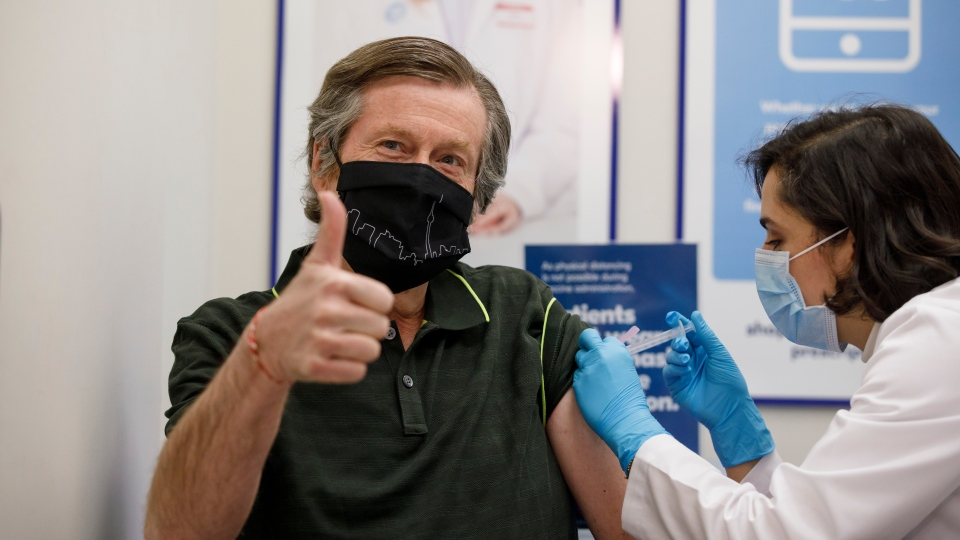 Toronto Mayor John Tory receives a dose of the AstraZeneca COVID-19 vaccine by pharmacist Niloo Saiy at a Shoppers Drug Mart pharmacy in Toronto, Saturday, April 10, 2021. THE CANADIAN PRESS/Cole Bursto