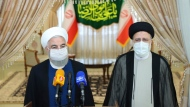 In this photo released by the official website of the office of the Iranian Presidency, President Hassan Rouhani, left, speaks with the media after his meeting with President-elect Ebrahim Raisi, right, who is current judiciary chief, in Tehran, Iran, Saturday, June 19, 2021. Iran's hard-line judiciary chief won the country's presidential election in a landslide victory Saturday, propelling the supreme leader's protege into Tehran's highest civilian position in a vote that appeared to see the lowest turnout in the Islamic Republic's history. (Iranian Presidency Office via AP)