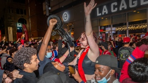 Montreal Canadiens fans celebrate their team's overtime victory over the Vegas Golden Knights in Game 3 of the NHL Stanley Cup semifinal outside of the Bell Centre in Montreal on Friday, June 18, 2021 in Montreal. THE CANADIAN PRESS/Peter McCabe