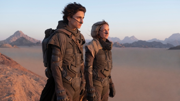"""This image released by Warner Bros. Entertainment shows Timothee Chalamet, left, and Rebecca Ferguson in a scene from the upcoming 2021 film """"Dune."""" Warner Bos. Pictures on Thursday announced that all of its 2021 film slate will stream on HBO Max at the same time they play in theaters. (Chia Bella James/Warner Bros. Entertainment via AP)"""