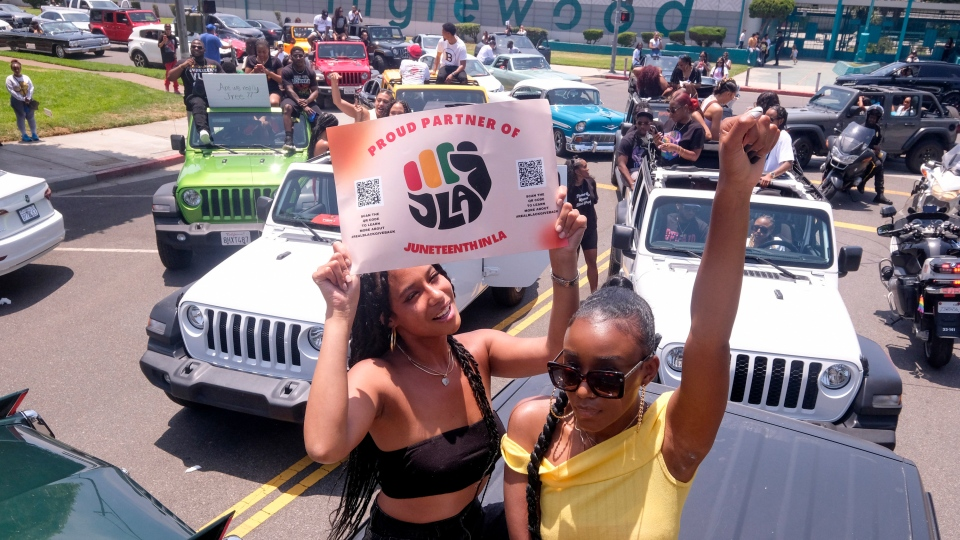 Jasmine Kingi, left, 26, and Robin Renee Green, 26, both from Los Angeles, celebrate as they take part in a car parade to mark Juneteenth, Saturday, June 19, 2021, in Inglewood, Calif. (AP Photo/Ringo H.W. Chiu)