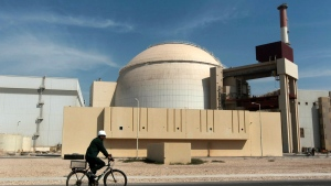 FILE - In this Oct. 26, 2010 file photo, a worker rides a bicycle in front of the reactor building of the Bushehr nuclear power plant, just outside the southern city of Bushehr. Iran's sole nuclear power plant has undergone a temporary emergency shutdown, state TV reported on Sunday, June 20, 2021. (AP Photo/Mehr News Agency, Majid Asgaripour, File)