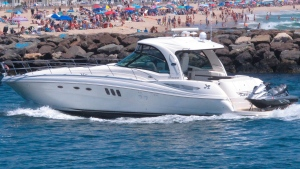 In this June 28, 2020, a yacht cruises through the Manasquan Inlet as a large crowd fills the beach in Manasquan, N.J. (AP Photo/Wayne Parry, File)