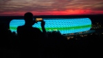 A man takes a photo of the illuminated Allianz Arena stadium as the sun sets on the day Germany face France during the Euro 2020 soccer championship group F competition in Munich, Germany, Tuesday, June 15, 2021. (Matthias Balk/DPA via AP)