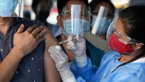 A health worker inoculates a man with China's Sinovac COVID-19 vaccine at a temporary vaccination center in Manila, Philippines, Tuesday, June 22, 2021. The Philippine president has threatened to order the arrest of Filipinos who refuse COVID-19 vaccination and told them to leave the country for hard-hit countries like India and the United States if they would not cooperate with massive efforts to end the pandemic. (AP Photo/Aaron Favila)