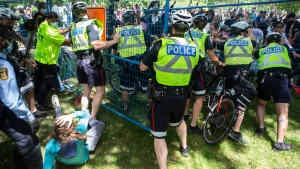 Police try to hold back protesters as they break through a fence during an eviction process at a homeless encampment in Toronto on Tuesday, June 22, 2021. THE CANADIAN PRESS/Chris Young