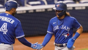 Toronto Blue Jays George Springer (4) congratulates Bo Bichette after Bichette scored during the sixth inning of a baseball game against the Miami Marlins, Tuesday, June 22, 2021, in Miami. (AP Photo/Marta Lavandier)