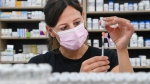 Barbara Violo, pharmacist and owner of The Junction Chemist Pharmacy, draws up a dose of the Pfizer-BioNTech COVID-19 vaccine, in Toronto, Friday, June 18, 2021. THE CANADIAN PRESS/Nathan Denette