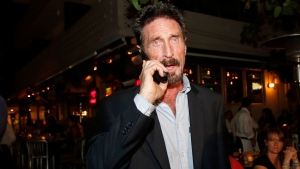 In this Dec 12, 2012 file photo, anti-virus software founder John McAfee talks on his mobile phone as he walks on Ocean Drive in the South Beach area of Miami Beach, Fla. John McAfee, the creator of the antivirus named after him, has been found dead in a cell of a jail near Barcelona, a government source told The Associated Press on Wednesday June 23, 2021 on the same day that a Spanish court issued a preliminary ruling in favor of his extradition to the United States to face tax-related criminal charges.(AP Photo/Alan Diaz, file)
