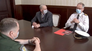 """In this photo taken from a video released by Russian Defense Ministry Press Service, Captain John Foreman, who is currently serving as the UK Defense Attaché in the British Embassy, right, attends a meeting in the Russian Defense Ministry in Moscow, Russia, Wednesday, June 23, 2021. The Defense Ministry said it called in the U.K. military attache in Moscow to protest the destroyer's """"dangerous move"""" and urged British authorities to investigate the crew's actions. (Russian Defense Ministry Press Service via AP)"""