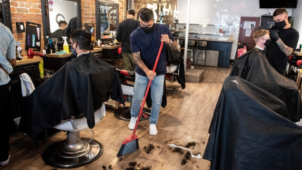 Owner Ankur Vadhera sweeps away hair at Capital Barber Shop in Ottawa, on its first day of reopening as Ontario moves into Stage 2 of its plan to lift lockdowns implemented in response to the COVID-19 pandemic, on Friday, June 12, 2020. THE CANADIAN PRESS/Justin Tang