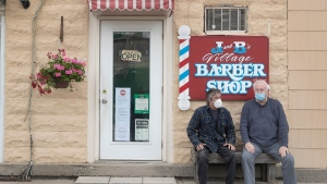 Customers wait their turn outside at J & B Barbershop in Fenelon Falls, Ontario on Friday June 12, 2020. With phase two easing of COVID-19 restrictions in central Ontario barber shops were allowed to reopen today with only one customer allowed at a time and masks mandatory. THE CANADIAN PRESS/Fred Thornhill