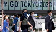 """Passers-by cross a street with a backdrop of an Olympics ad sign in Tokyo, Friday, June 25, 2021. A """"no-spectator games"""" remains an option for the Tokyo Olympics, the president of the Tokyo Olympic organizing committee, said on Friday. (AP Photo/Shuji Kajiyama)"""