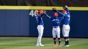 Toronto Blue Jays' Teoscar Hernandez, left, Jonathan Davis and George Springer, right, celebrate the team's 6-3 win over the Tampa Bay Rays in a baseball game in Buffalo, N.Y., Saturday, July 3, 2021. (AP Photo/Adrian Kraus)