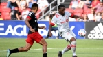 Toronto FC's Ayo Akinola, right, shoots and scores in front of D.C. United's Andy Najar during the first half of an MLS soccer match Saturday, July 3, 2021, in Washington. (Will Newton/The Washington Post via AP)