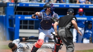Tampa Bay Rays' Yandy Diaz, left, scores a run as Toronto Blue Jays catcher Danny Jansen, center, throws to third for an out against Austin Meadows during the sixth inning of a baseball game in Buffalo, N.Y., Sunday, July 4, 2021. (AP Photo/Adrian Kraus)