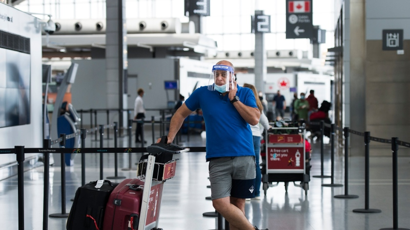 A man wearing a mask and full face shield talks on the phone at Toronto's Pearson International Airport during the COVID-19 pandemic in Toronto on Tuesday, June 23, 2020. THE CANADIAN PRESS/Nathan Denette