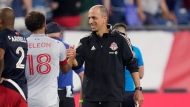 Toronto FC interim coach Javier Perez, right, is congratulated by midfielder Nick DeLeon (18) at the conclusion of the second half of an MLS soccer match against the New England Revolution, Wednesday, July 7, 2021, in Foxborough, Mass. Toronto won 3-2. (AP Photo/Charles Krupa)