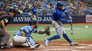 Umpire Vic Carapazza, left, and Tampa Bay Rays catcher Mike Zunino, center, look as Toronto Blue Jays' George Springer hits an RBI-single to center field during the third inning of a baseball game Friday, July 9, 2021, in St. Petersburg, Fla.(AP Photo/Steve Nesius)