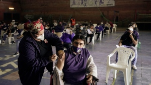 A healthcare worker inoculates David Flecha with a dose of the Sputnik V COVID-19 vaccine, during a vaccination campaign for the vulnerable between the ages of 18-50 at a sports center converted into a vaccination site, in Asuncion, Paraguay, Saturday, July 3, 2021.  (AP Photo/Jorge Saenz)