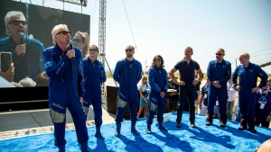 Virgin Galactic founder Richard Branson, far left, accompanied by his crew, speaks to the crowd while celebrating their flight to space from Spaceport America near Truth or Consequences, N.M., Sunday, July 11, 2021. (AP Photo/Andres Leighton)