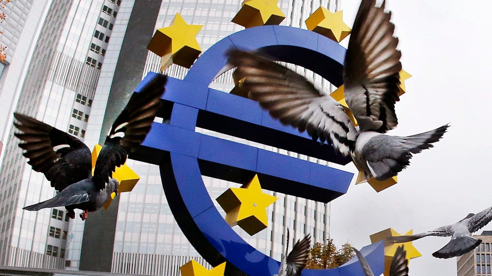 In this Thursday, Nov. 10, 2016 filer, Pigeons fly in front of the Euro sculpture at the old European Central Bank bulding in Frankfurt, Germany. (AP Photo/Michael Probst, File )