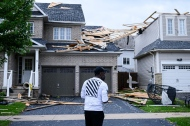 A resident surveys the damage left after a tornado touched down in his neighbourhood, in Barrie, Ont., on Thursday, July 15, 2021. THE CANADIAN PRESS/Christopher Katsarov