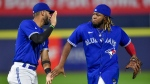 Toronto Blue Jays' Vladimir Guerrero Jr., right, celebrates with Lourdes Gurriel Jr. after the team's win over the Texas Rangers in a baseball game in Buffalo, N.Y., Friday, July 16, 2021. (AP Photo/Adrian Kraus)
