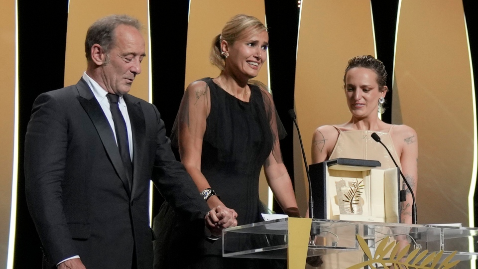 Vincent Lindon, from left, director Julia Ducournau, and Agathe Rousselle accept the Palme d'Or for the film 'Titane' during the awards ceremony for the 74th international film festival, Cannes, southern France, Saturday, July 17, 2021. (AP Photo/Vadim Ghirda)