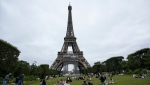 People relax at the Champ-de-Mars garden next to the Eiffel Tower in Paris, Friday, July 16, 2021. (AP Photo/Michel Euler)
