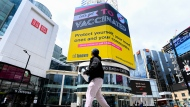 A man looks up at an electronic COVID-19 vaccination sign at Dundas Square during the COVID-19 pandemic in Toronto on Tuesday, May 11, 2021. THE CANADIAN PRESS/Nathan Denette