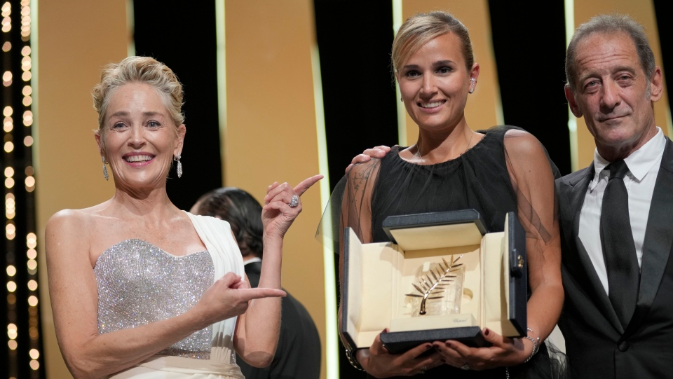 Director Julia Ducournau, centre, holds the Palme d'Or for the film 'Titane' as she poses with Sharon Stone, left, and Vincent Lindon during the awards ceremony at the 74th international film festival, Cannes, southern France, Saturday, July 17, 2021. (AP Photo/Vadim Ghirda)