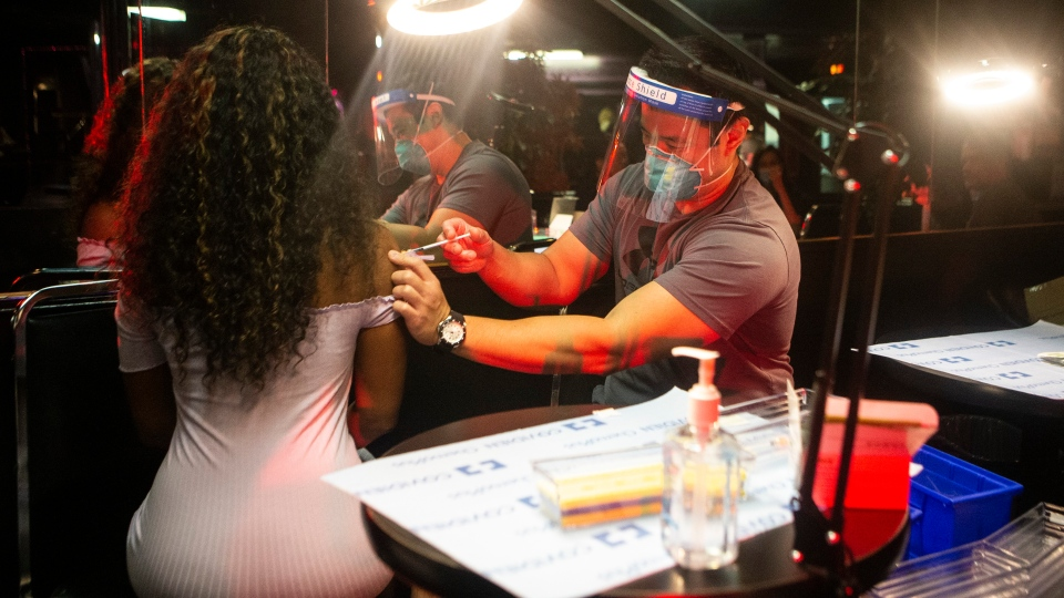 A physician with the University Health Network administers a vaccine at a pop-up clinic at Filmore's adult entertainment club in downtown Toronto, on Saturday, July 17, 2021. THE CANADIAN PRESS/Chris Young