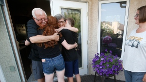 Richard and Linda Davis hug their grandchildren Miles and Linda Carnegie as their daughter, Michelle Carnegie, looks on at their home in Winnipeg, Sunday, July 18. The couple were able to hug their grandchildren for the first time in fifteen months when Manitoba lifted some COVID-19 restrictions this weekend. THE CANADIAN PRESS/John Woods