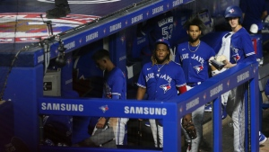 Toronto Blue Jays players and staff, including Vladimir Guerrero Jr., center left, and Lourdes Gurriel Jr., center right, leave the dugout after a baseball game against the Boston Red Sox on Wednesday, July 21, 2021, in Buffalo, N.Y. After a road trip, the Blue Jays will resume playing home games in Toronto. (AP Photo/Joshua Bessex)