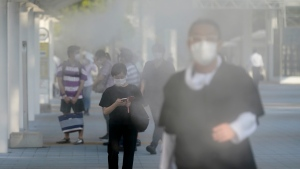 Pedestrians walk through misters before the start of the 2020 Summer Olympics, Thursday, July 22, 2021, in Tokyo, Japan. (AP Photo/Seth Wenig)
