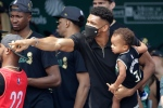 Milwaukee Bucks' Giannis Antetokounmpo points to the crowd as he holds his song, Liam, during a parade celebrating the Milwaukee Bucks' NBA Championship basketball team Thursday, July 22, 2021, in Milwaukee. (AP Photo/Aaron Gash)